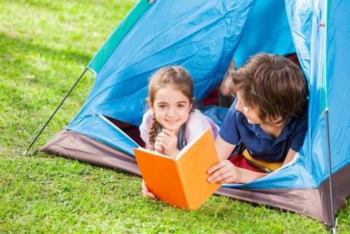 Niños leyendo libros de Isadora Moon en una tienda de campaña.