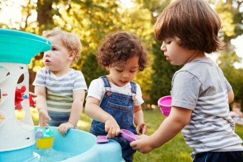 Niños jugando al aire libre con agua y formando parte de un experimento.