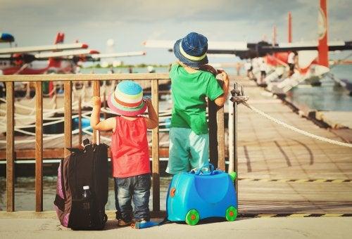 Niños mirando aviones antes de volver de su viaje al extranjero con sus padres.