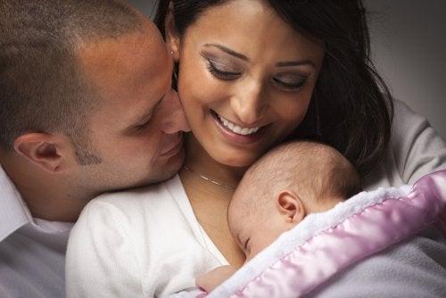 Padres realizando los cuidados del bebé pertinentes con su recién nacido.