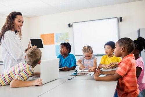 Profesora dando clase a sus alumnos con una tablet en la mano.