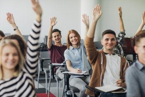 Alumnos con las manos levantadas con ganas de aprender.