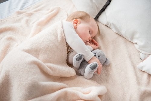 Bebé durmiendo abrazado a su peluche.