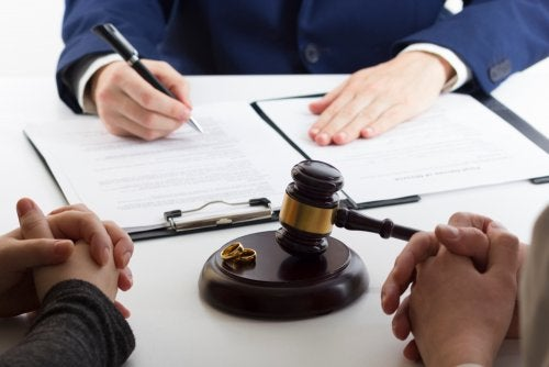 Firma de capitulaciones matrimoniales de una pareja con su abogado.