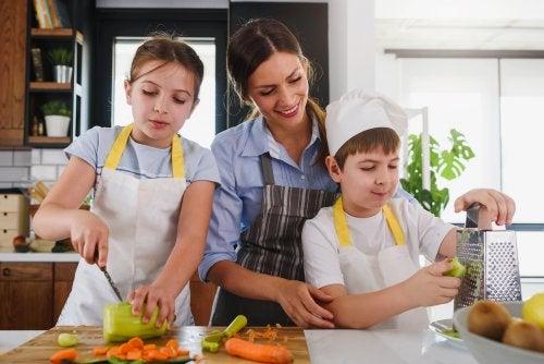 Madre cocinando con sus hijos para enseñarles la disciplina en la alimentación saludable.