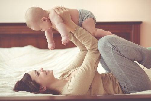 Mamá jugando con su bebé en la cama para estimular el desarrollo de los sentidos.