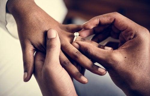Pareja poniéndose el anillo en la boda y decidiendo entre los diferentes tipos de regímenes matrimoniales.