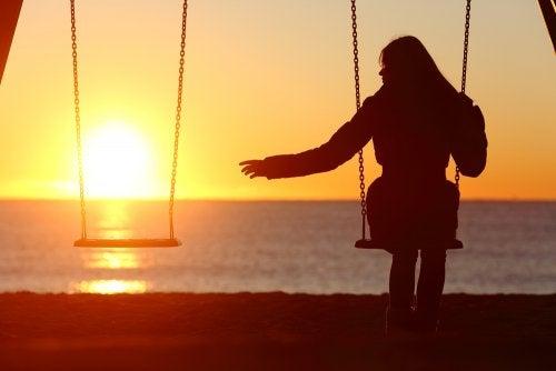 Mujer viuda sola en un columpio pensando en la pensión de viudedad.