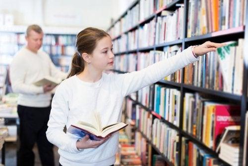 Niña en la biblioteca buscando libros que hayan ganado el Premio El Barco de Vapor.
