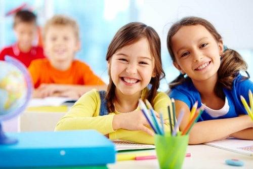 Niñas felices en clase tras el cambio de colegio.