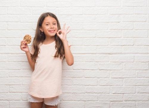 Niña recibiendo una galleta a modo de refuerzo positivo por su buen comportamiento y las pegatinas recibidas en el sistema de economía de fichas.