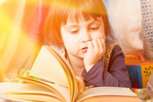 Niña leyendo uno de los libros infantiles informativos que proponemos en este artículo.