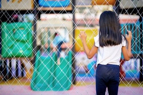Niña víctima de abusos mirando a través de una valla cómo juegan unos niños en el parque.