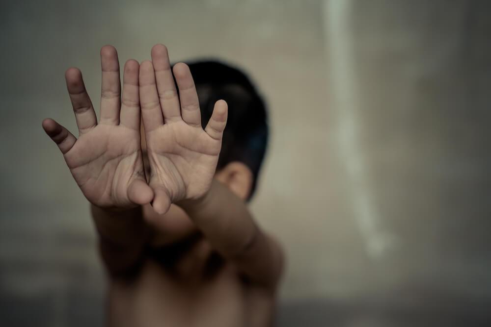 Enfant aux mains levées victime de maltraitance.