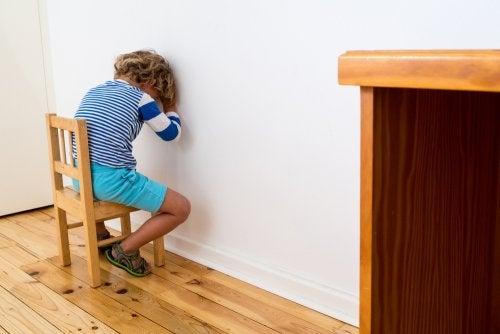 Niño castigado cara a la pared.