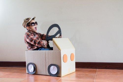 Niño jugando con su coche hecho de cartón.