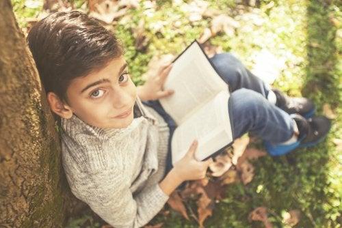 Niño leyendo uno de los libros recomendados para niños de 7 a 9 años sentado en un parque con hojas por el suelo.