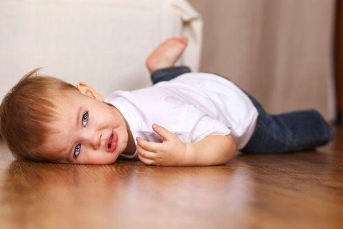 Niño tumbado en el suelo aprendiendo a gestionar sus rabietas gracias a los libros infantiles.
