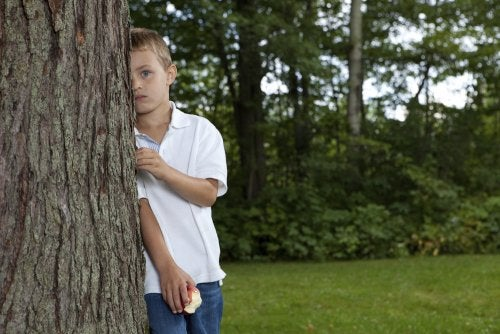 Niño tímido e introvertido escondido detrás de un árbol que debería leer algunos libros infantiles para dejar la timidez a un lado.