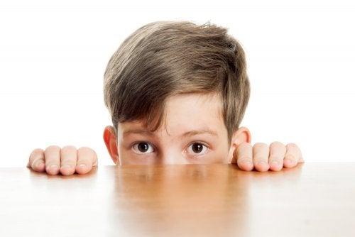 Nio tímido o introvertido escondido detrás de una mesa asomando solo los ojos.