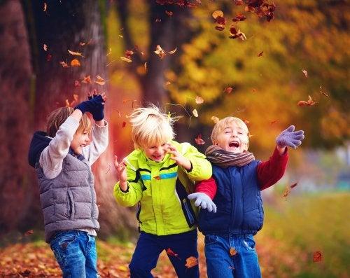 Niños jugando con las hojas del parque en otoño.