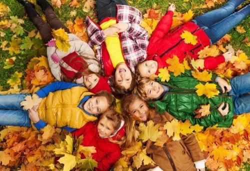 Niños tumbados sobre las hojas caídas del otoño.