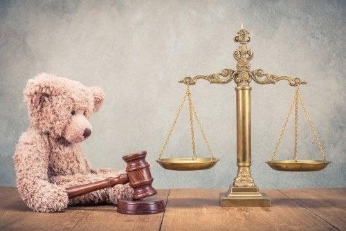 Osito de peluche y balanza de la justicia para representar los juicios de familia.