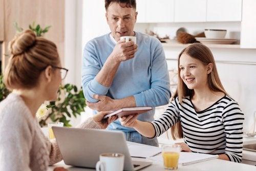 Niña con sus padres en la cocina con una buena actitud tras su educación mediante el refuerzo positivo y negativo.