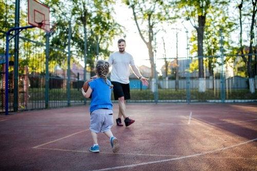Padre jugando con su hija al baloncesto.