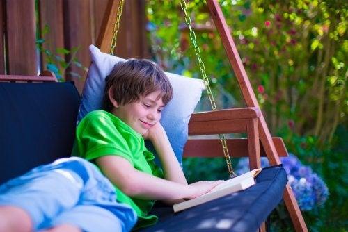 Niño leyendo uno de los libros de Manolito Gafotas en un columpio.