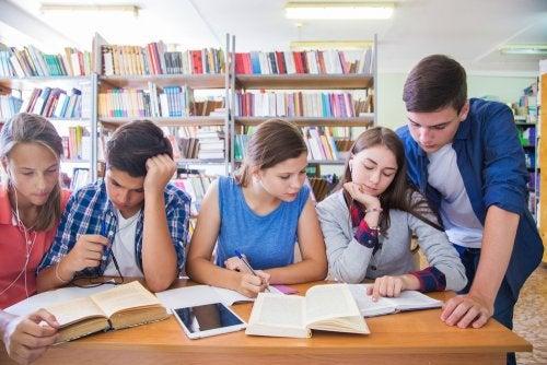 Adolescentes en la biblioteca estudiando con una gran motivación escolar.