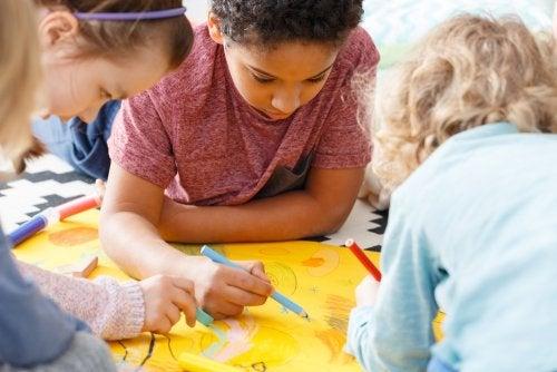 Niños trabajando en grupo a los que han hecho una foto para publicar en el periódico del colegio.