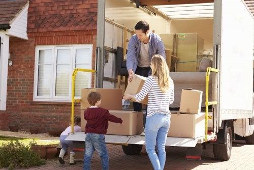 Familia descargando del camión las cajas de las mudanzas, que son difíciles en la infancia.