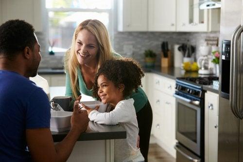 Familia en la cocina de casa hablando sobre criar a niños biculturales con su hija.