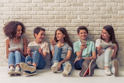 Grupo de amigos con sus smartphones en la adolescencia.