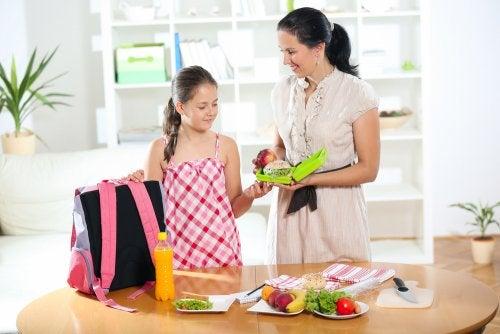 Madre e hija preparando el almuerzo para tener un buen día de colegio.