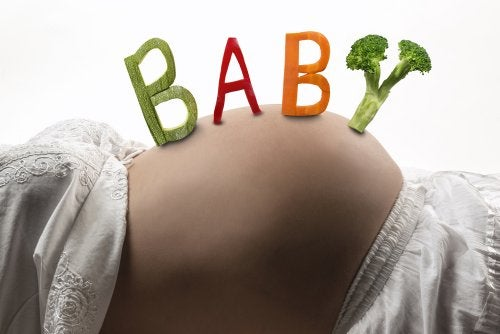 Mujer embarazada con palabra 'baby' en la barriga escrita con comida.