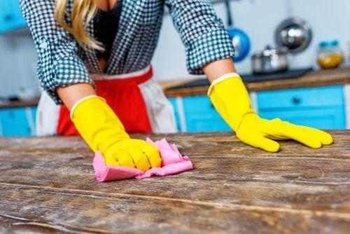 Mujer limpiando la cocina como parte del trabajo doméstico.