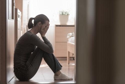 Mujer sentada en el suelo con depresión postparto.