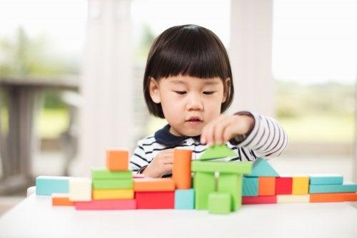 Niña jugando con bloques para su desarrollo mediante la herencia y el ambiente.