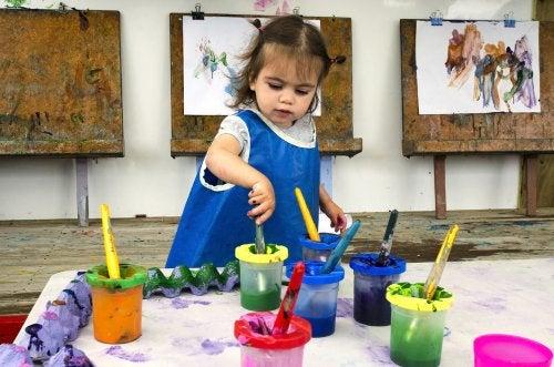 Niña pintando cuadros para desarrollar su talento artístico en preescolar.