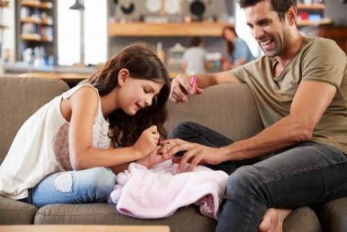 Niña pintándole las uñas a su padre.