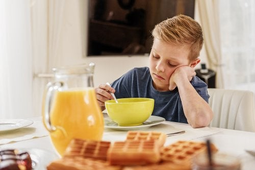 Niño desayunando muy triste decepcionado porque no ha conseguido entrar en el equipo de fútbol que quería.