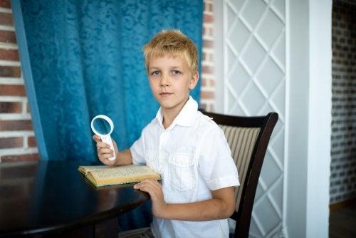 Niño con una lupa como los protagonistas de los libros infantiles sobre detectives.