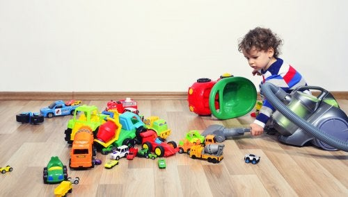 Niño con todos sus juguetes por el suelo sin ordenar.