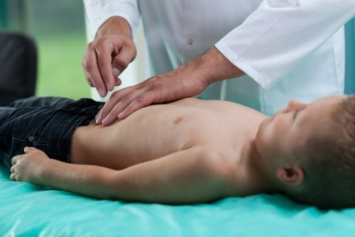 Niño siendo reconocido por un médico debido a su enfermedad de Crohn.