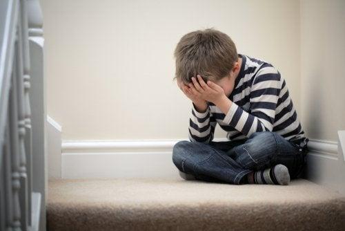 Niño sentado en las escaleras de su casa muy triste porque no saber cómo gestionar la decepción que siente con sus amigos.