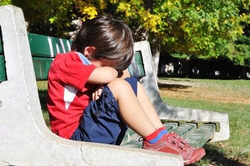 Niño triste sentado en un banco del parque porque no le han invitado al cumpleaños.