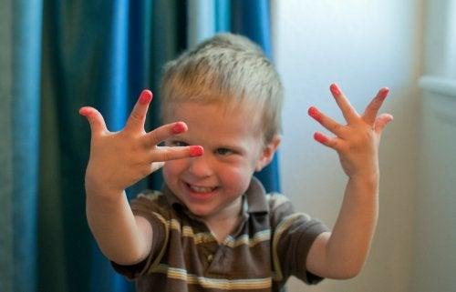 Niño con las uñas pintadas de rosa.