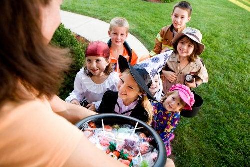 Niños pidiendo caramelos en una casa por Halloween.